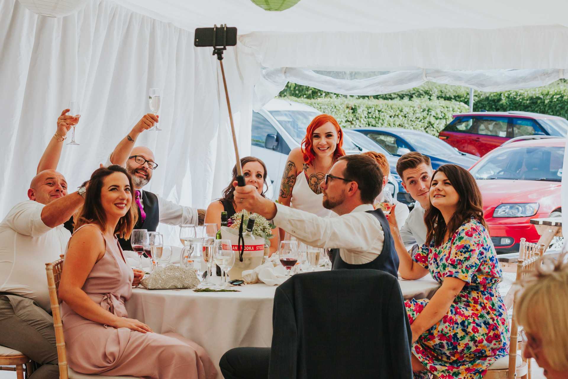 guests sat round a table taking a selfie with the bride