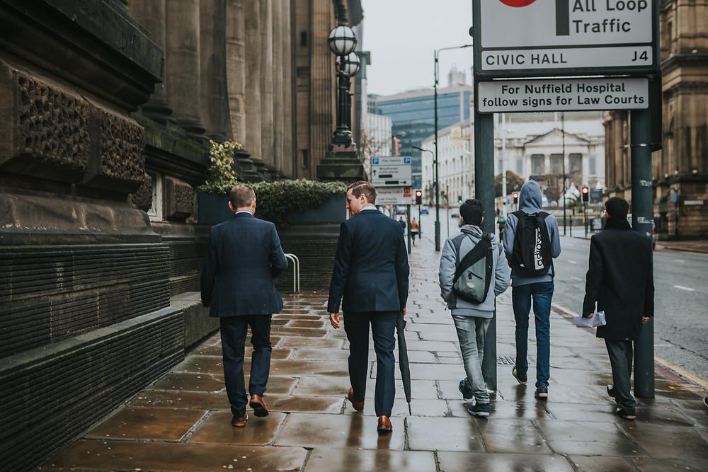 Groom and best man walking past Leeds Town Hall