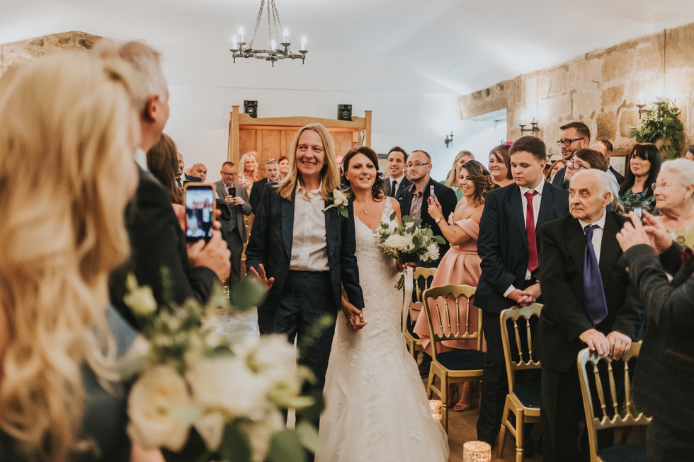 Brides walking down the aisle together at Danby Castle