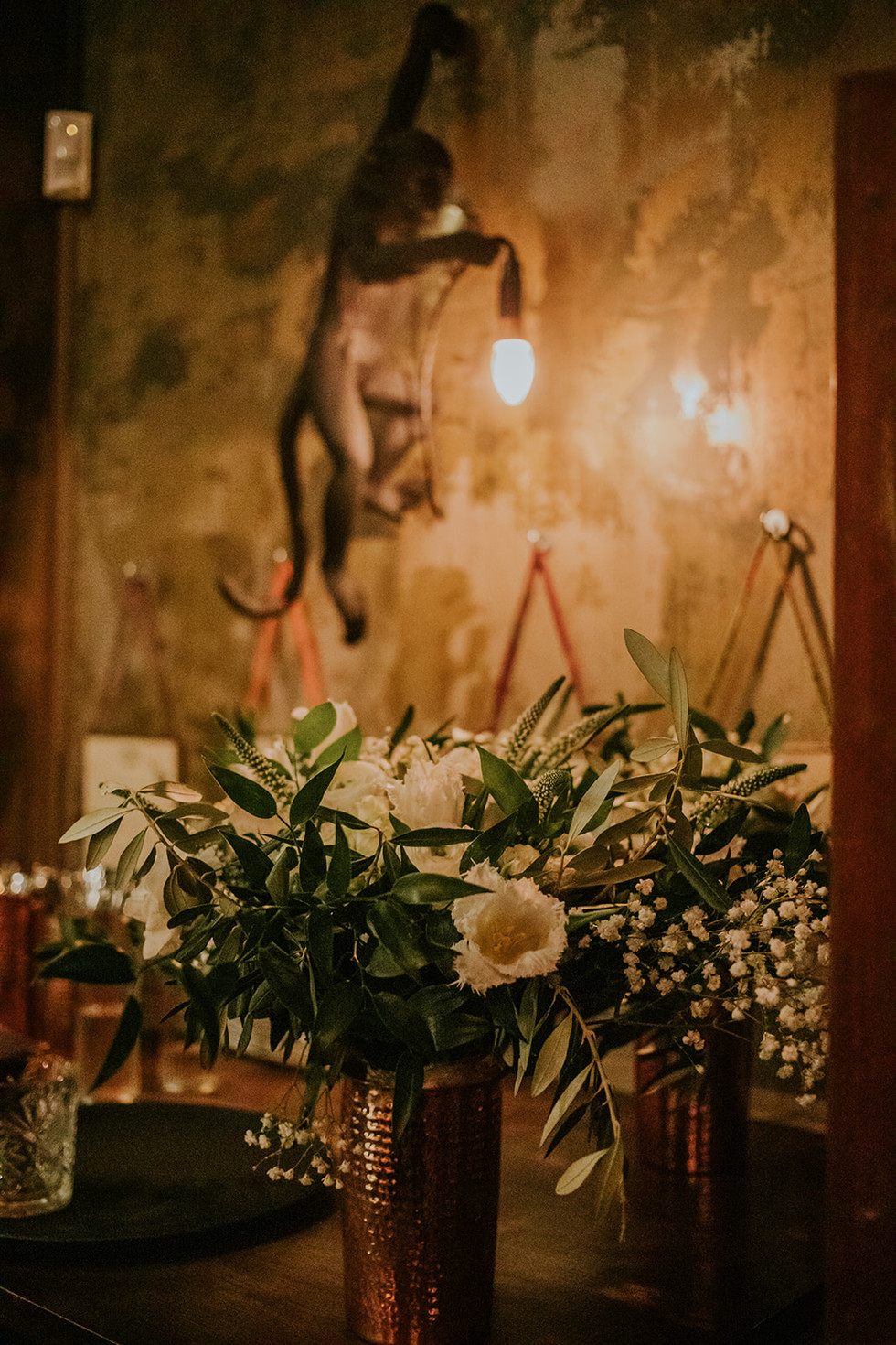 wedding flowers underneath a monkey holding a light