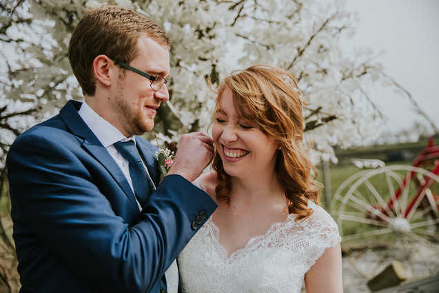 Groom brushing hair from brides face at the moorlands in halifax