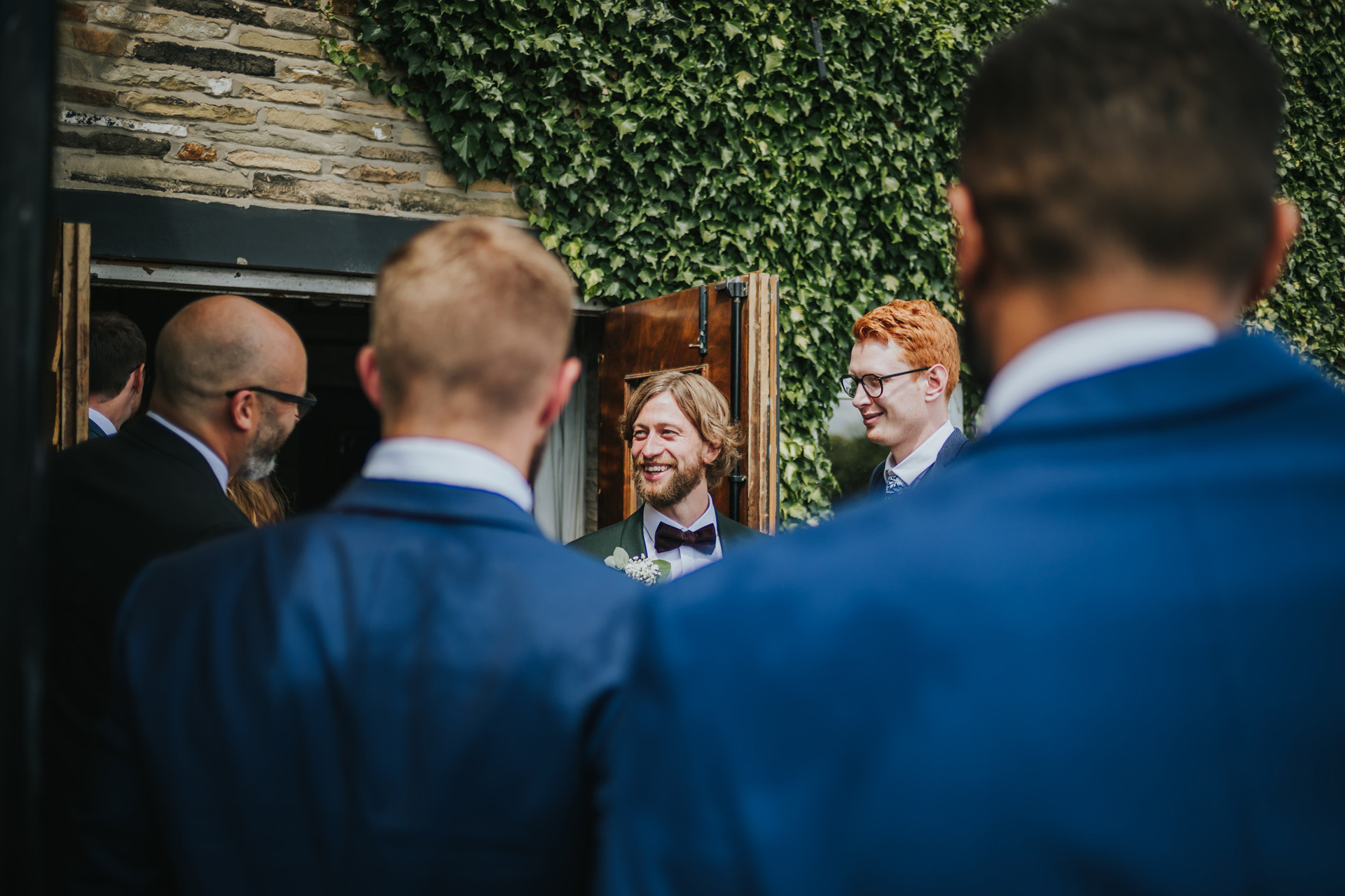 The groom chatting with friends outside the pub