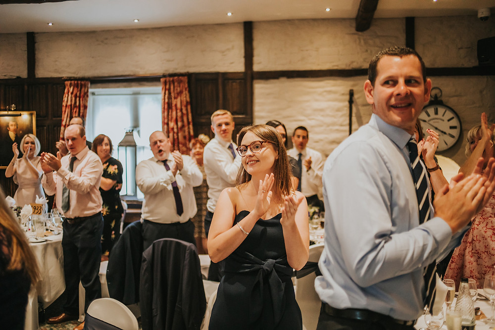guests clapping as the couples enter the room for the wedding breakfast