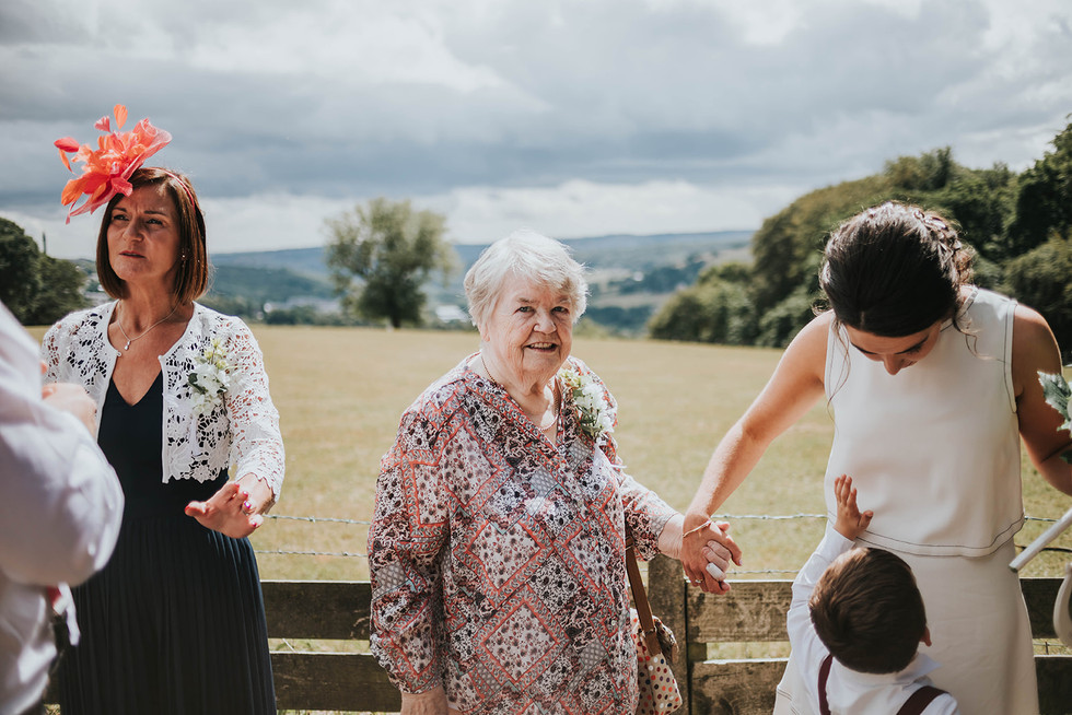 bride holding grans hand getting ready for group photos in Warley, halifax