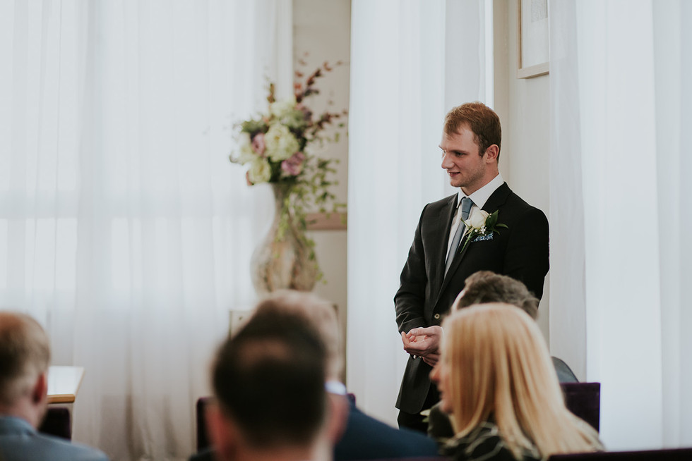 groom waiting at the front of the ceremony room