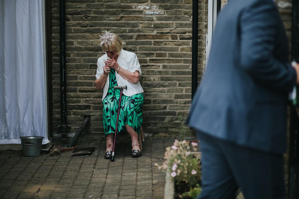 wedding guest lighting a cigarette