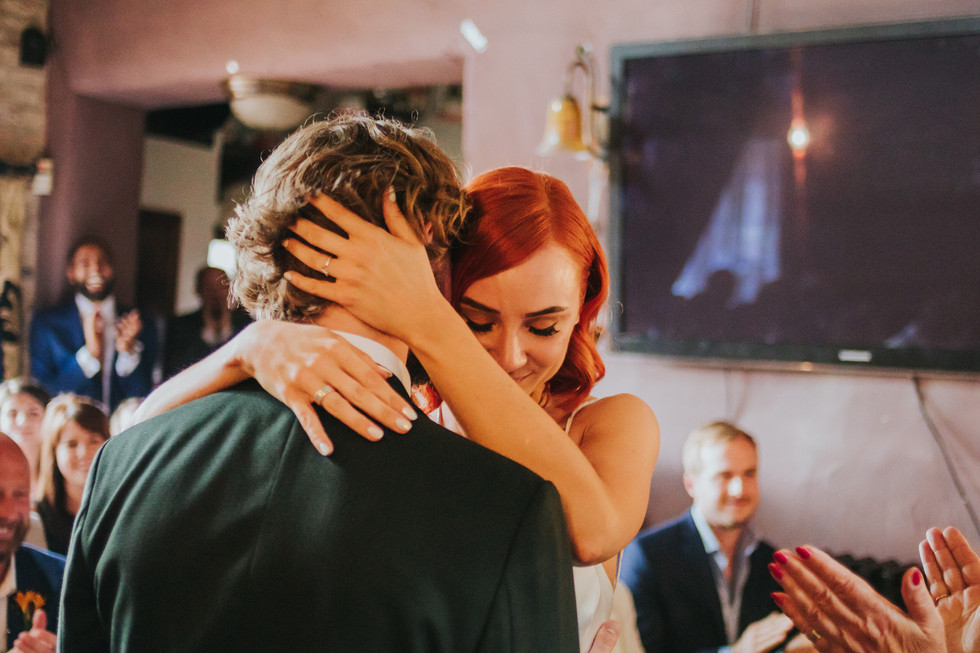 bride and groom hugging after exchanging rings