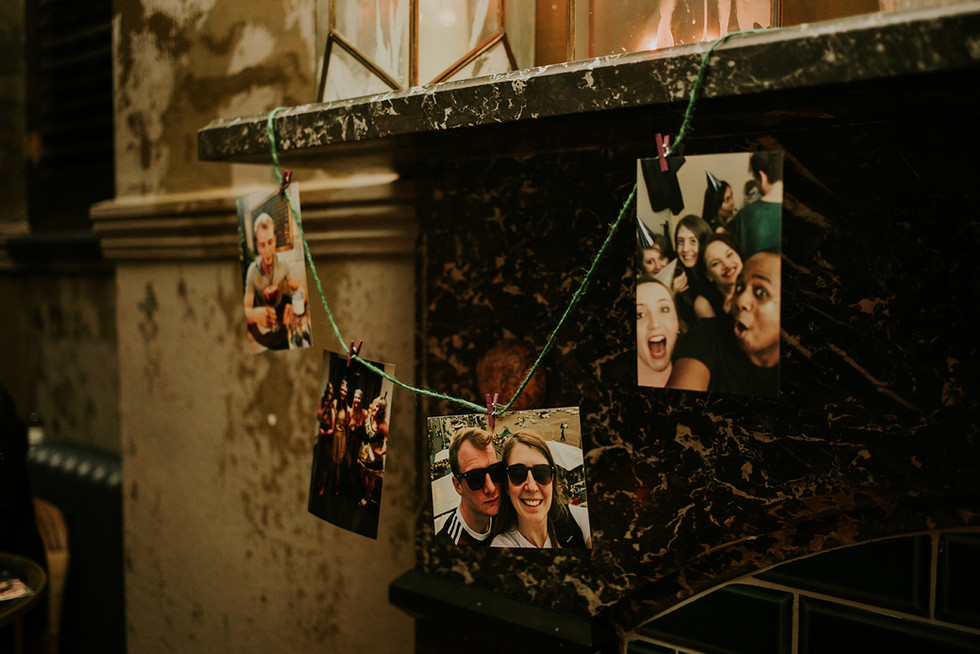 a string of photographs hung from a fireplace
