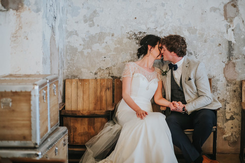 bride and groom sitting against a wall in Holmes Mill kissing