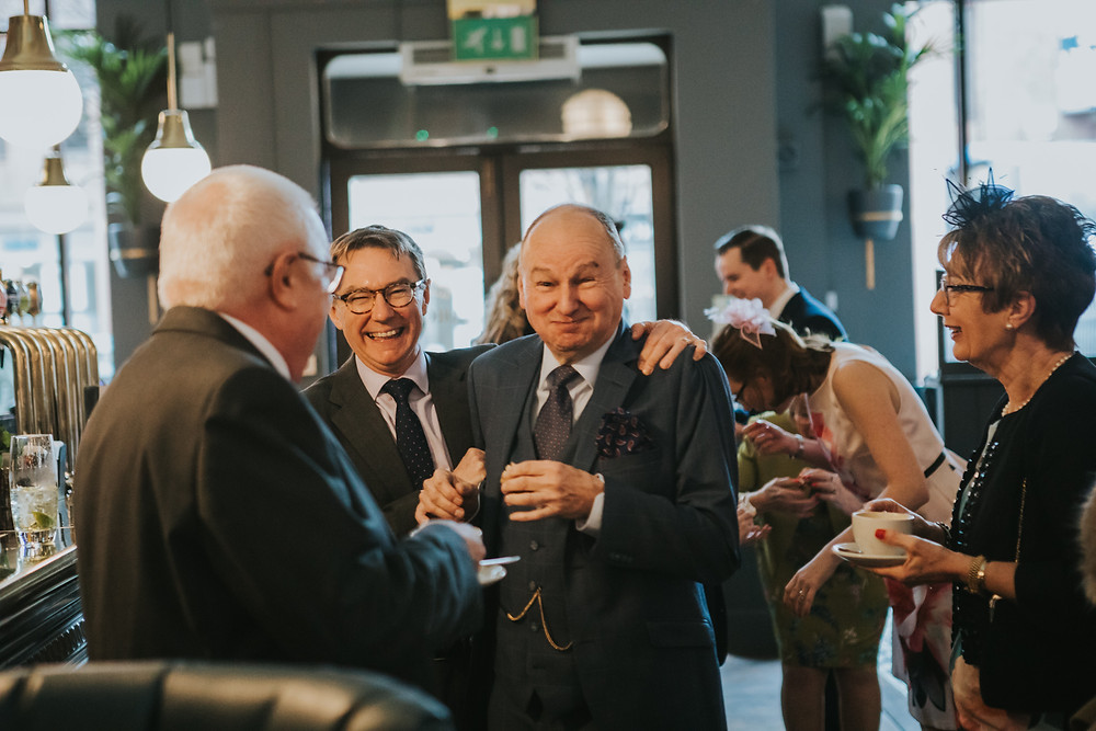 Wedding guests laughing in Browns bar