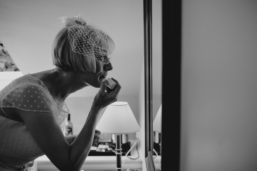 Bride looking a mirror and putting on her lipstick in the bridal suite at Holdsworth House