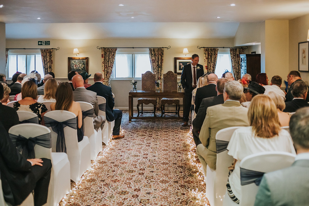 the groom waiting in the ceremony room at Holdsworth House