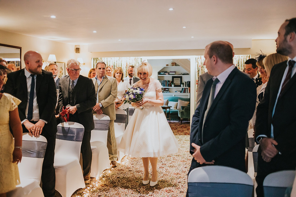 Bride smiling walking down the aisle by herself at holdsworth house