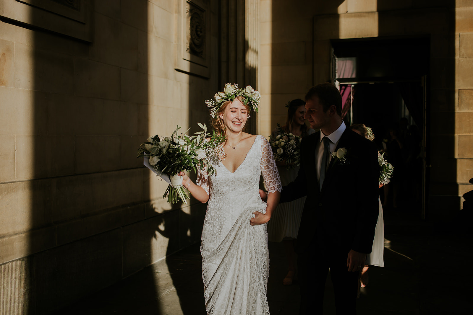 sun shining on the bride holding her flowers and wearing a flower crown
