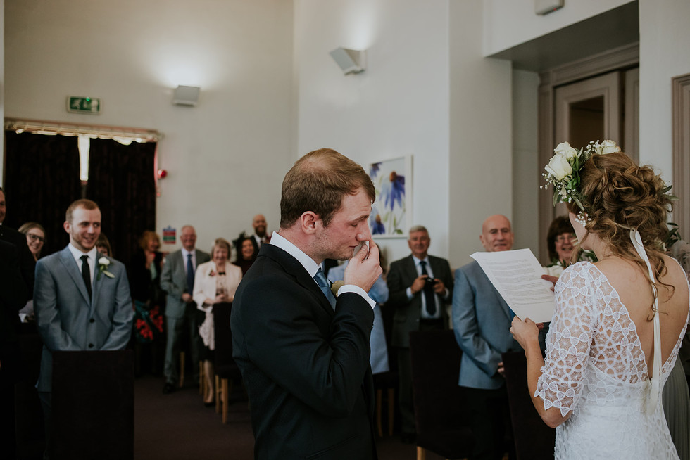 groom crying at the brides reading in the ceremony room at leeds town hall