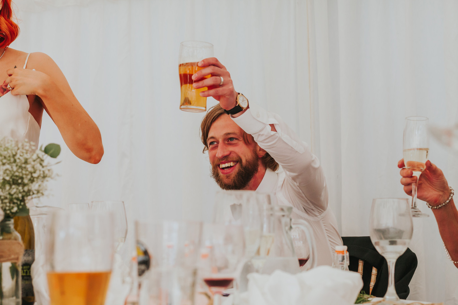 groom holding a beer toasting during the speeches