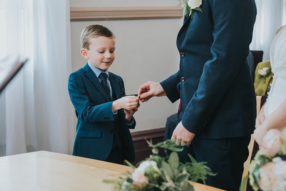 young boy hands wedding ring to the groom