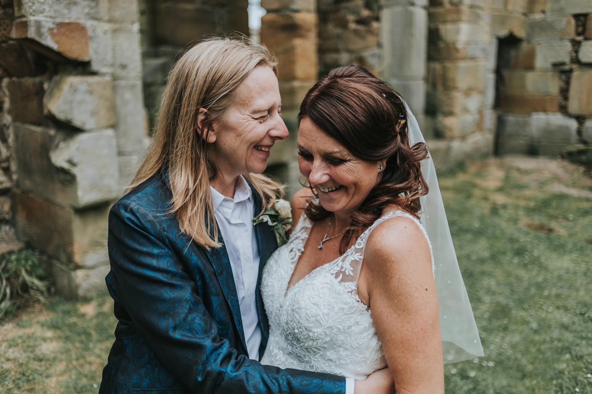 Brides smiling together at Danby Castle