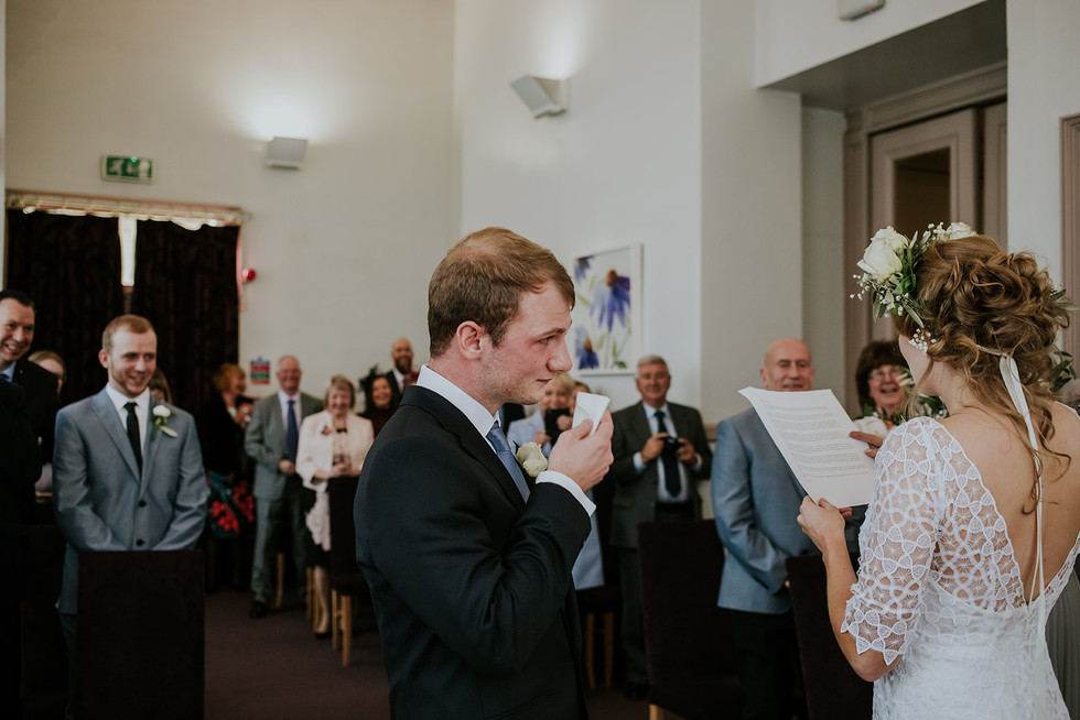 groom wiping his tears whilst the bride gives a reading