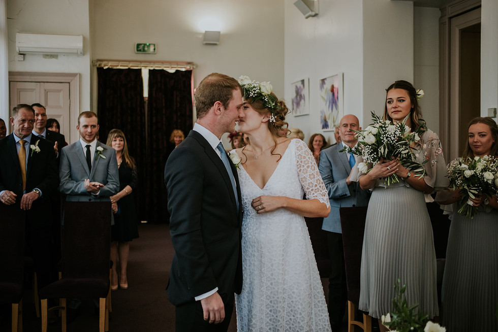 bride and groom kiss in fron of happy guests