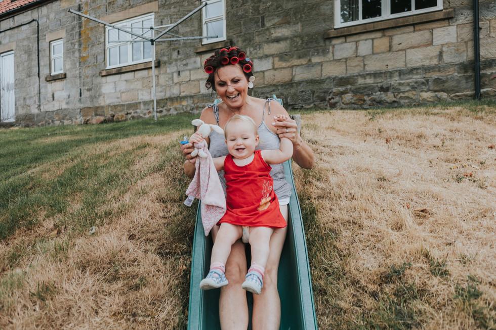 bride and toddler grandaughter on a slide