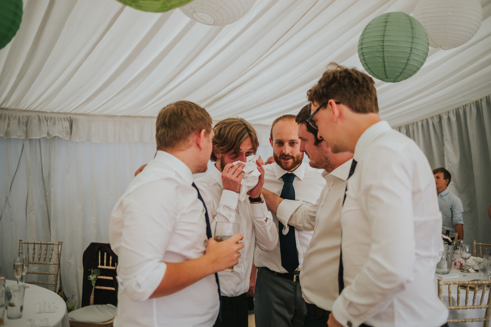 groom crying surrounded by his friends after the wedding speeches