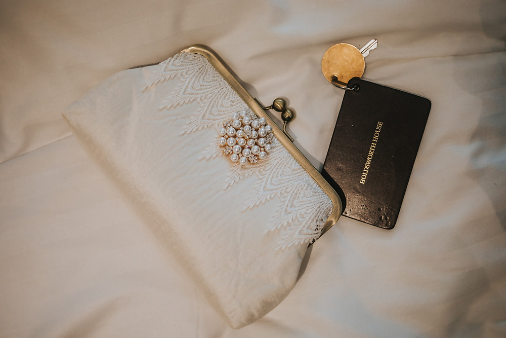 Brides handbag and Holdsworth House room key on bed in bridal suite