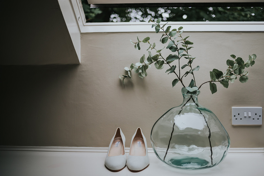 Brides shoes next to a plant at Holdsworth House