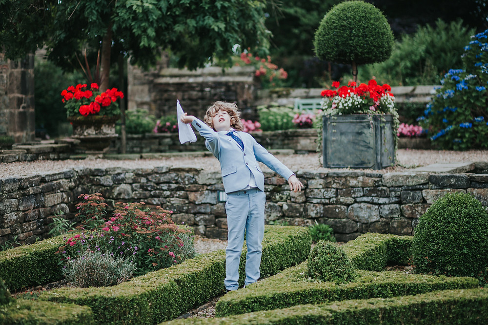 boy throwing a paper aeroplane in the maze at holdsworth house