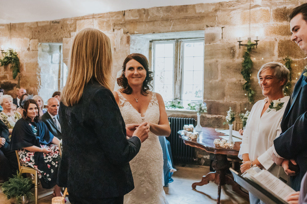 Two brides exchanging rings at Danby Castle in North Yorkshire