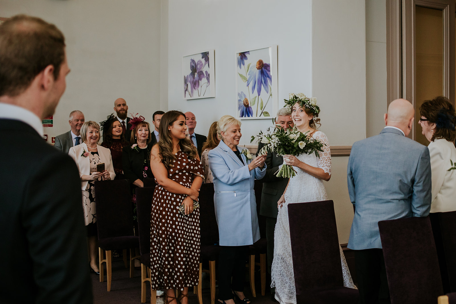 bride walking in, smiling at the groom, all the guests watching and smiling