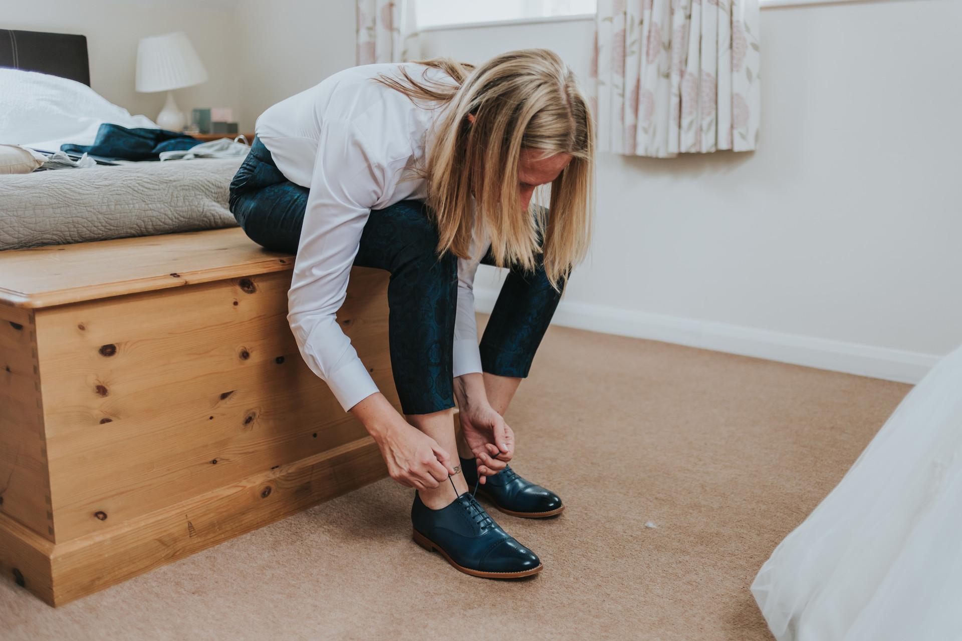 bride fastening her wedding shoes