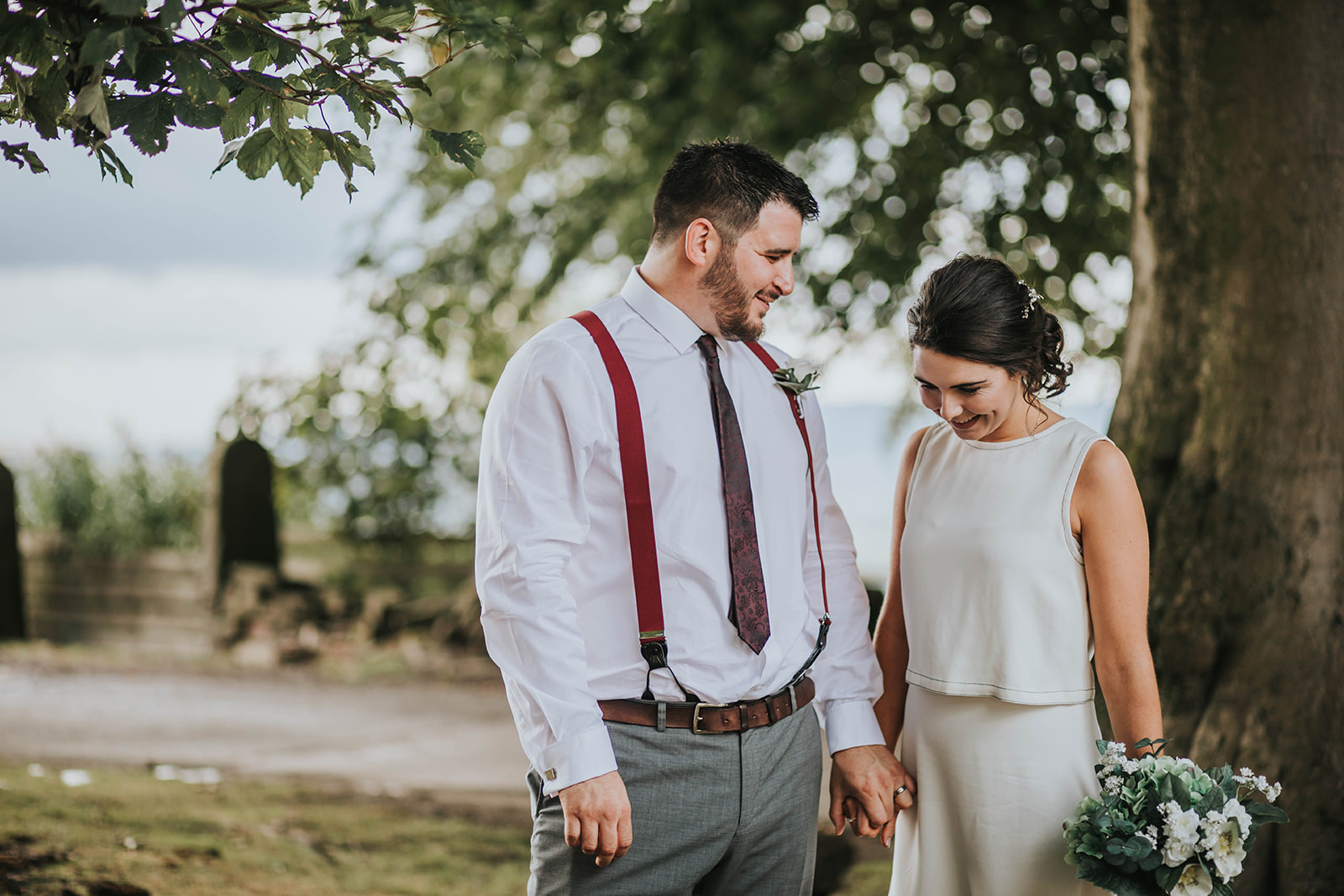natural relaxed bride and groom next to tree in the sunshine