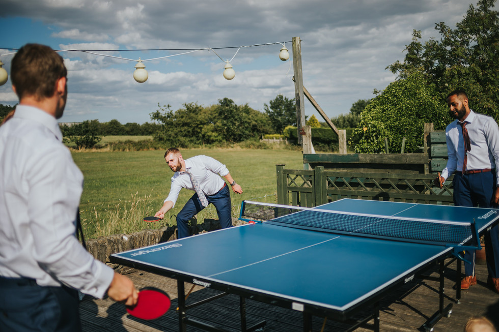guests outside in the sunshine playing ping pong
