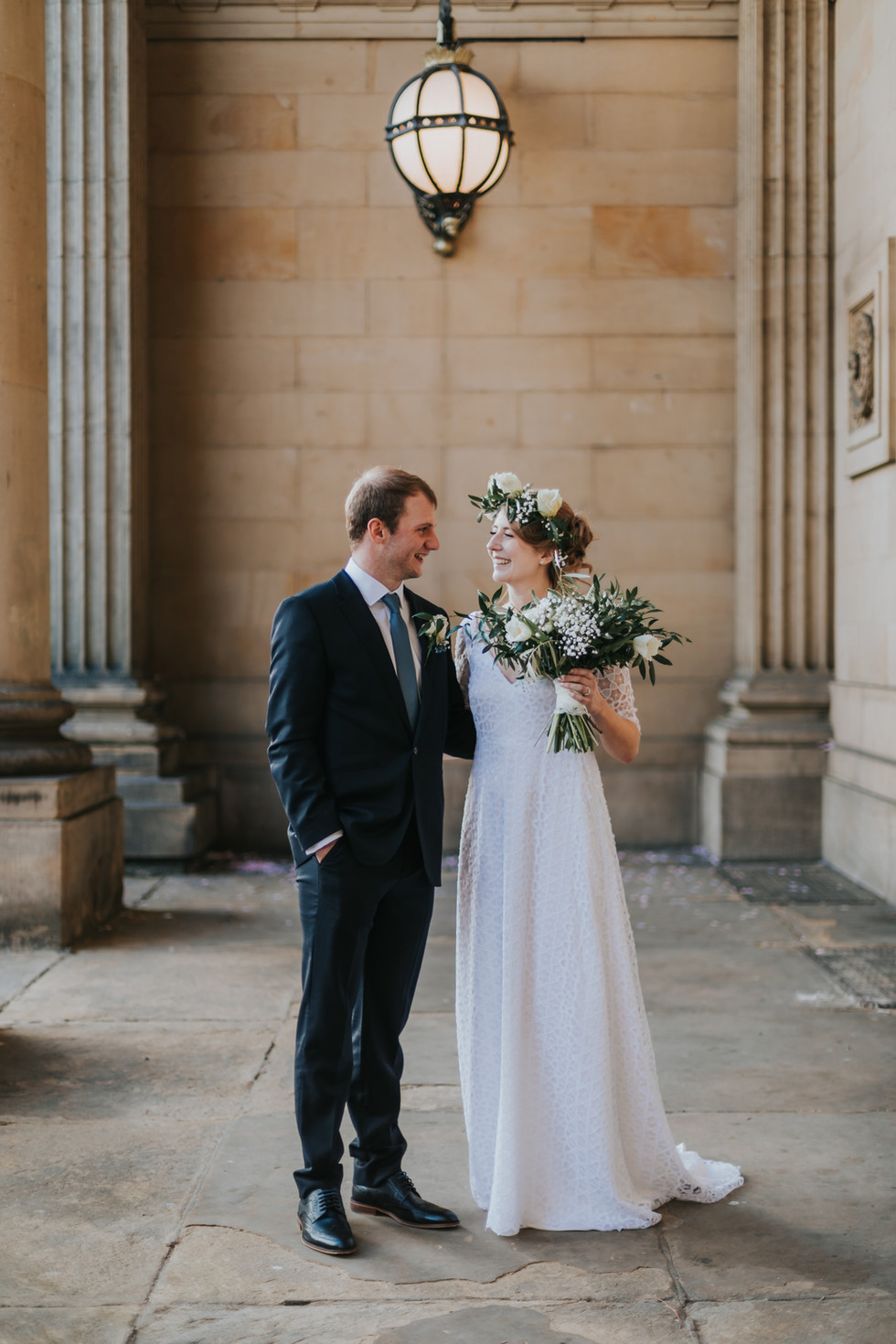 bride wearing a boho dress and a flower crown holding a bouquet looking at the groom outside leeds town hall