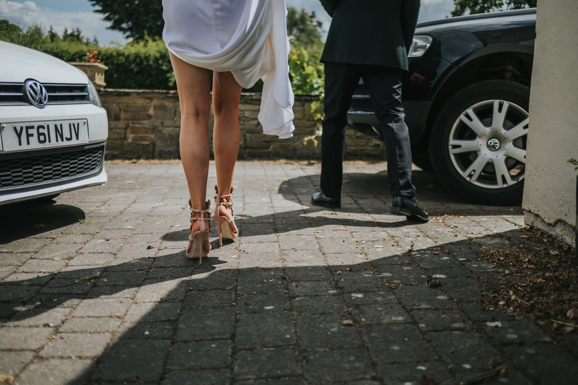 brides legs and amazing wedding shoes as she walks down the driveway