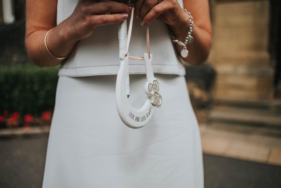 bride holding a traditional wedding horseshoe