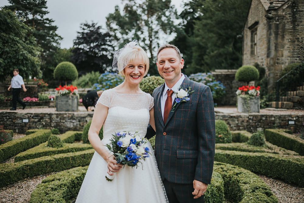 Bride and groom in front of the maze in the gardens at holdsworth house