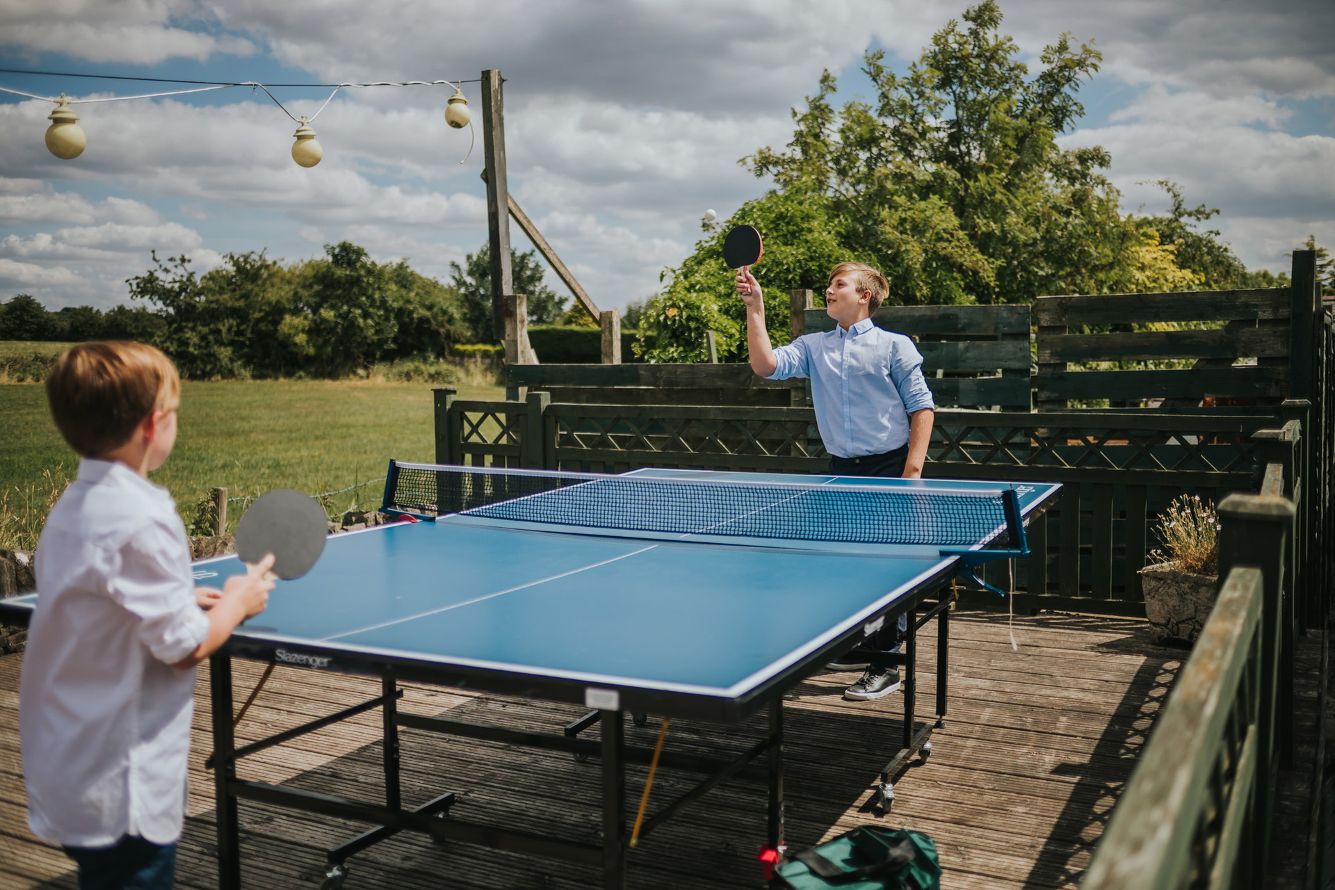 two boys playing table tennis outside the pub wedding venue