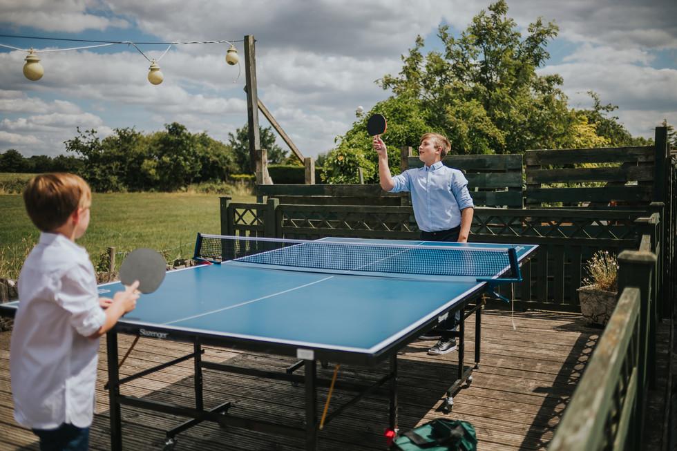 two boys playing table tennis outside the pub wedding venue