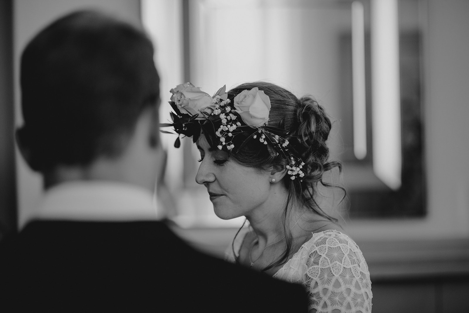 looking over the grooms shoulder at the bride in her flower crown