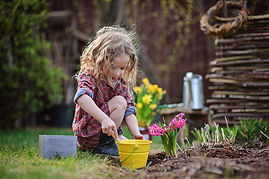 cute child girl plays little gardener an