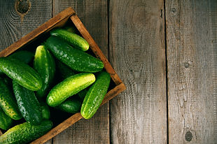 Cucumbers in a box on a wooden backgroun