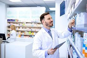 Handsome male pharmacist in white coat w