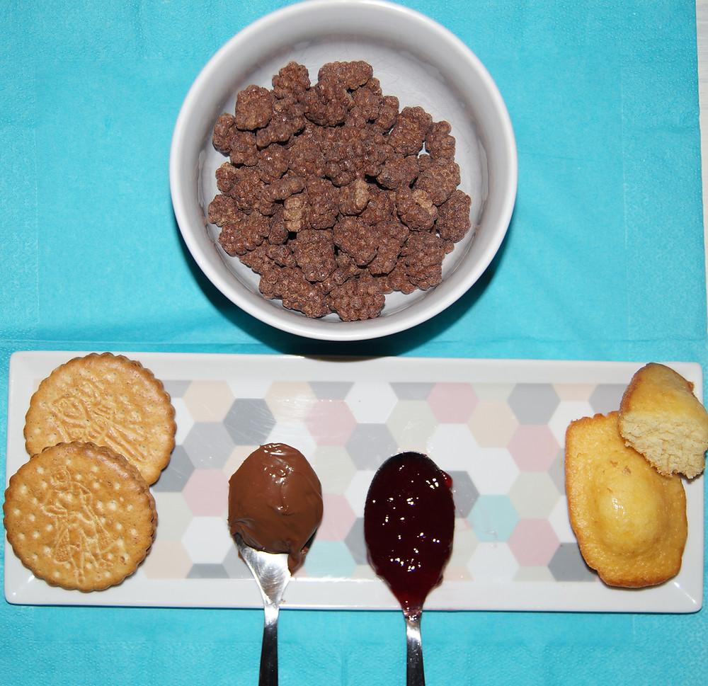 60g de céréales, 2 biscuits au chocolat, 1 c.à soupe de pâte à tartiner, 1 c. à soupe de confiture, 1 madeleine et 1/2