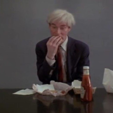 Andy Warhol eats a hamburger and ketchup.