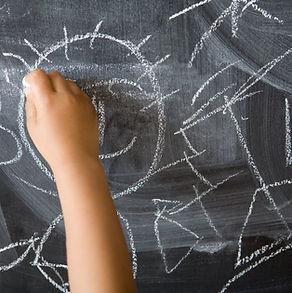 Child drawing on chalkboard