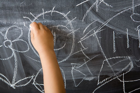 Image of a child's hand drawing a son on a blackboard. Other scribbles are visible on the blackboard in addition.