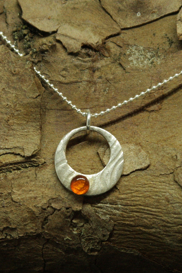4294 - Textured circle with offset circle aperture and amber cabochon