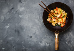 Stir fry noodles in traditional Chinese wok, chopsticks, ingredients. Space for text. Asian noodles